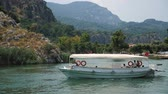 Dalyan, Turkey - 9 June: excursion boat with people floating on a narrow river in the summer June 9, 2019
