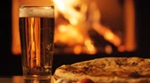 maltês : One glass of beer and pizza over fireplace background.