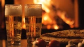 maltês : Two glasses of beer and pizza over fireplace background.
