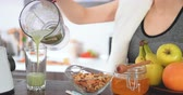 sportwear : Young woman making green juice with juice machine. Stock Footage