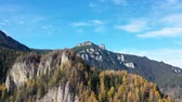 Moving out drone of beautiful mountain, autumn forest with yellow larch trees and rock formations.