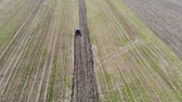 Tractor plowing the field prepairing for spring planting, aerial view