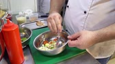 cook pours sauce and vegetables mixed with spoon. Stok Video