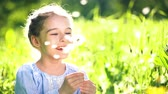 delicato : Beautiful little girl at sunny summer day blowing dandelion on green meadow. Summer fun concept. Filmati Stock