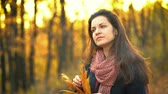 Young beautiful woman in sunny autumn park Стоковые видеозаписи