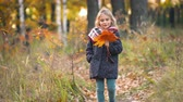 Little girl walking with autumn leaves in the park