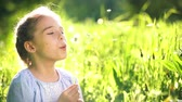 aspirations : Beautiful little girl at sunny summer day blowing dandelion on green meadow. Summer fun concept. Slow motion. Stock Footage