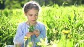Beautiful little girl at sunny summer day playing with flowers on green meadow. Summer fun concept.