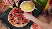 paprika salami : Three kids adding the grated cheese to raw pizza