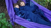 forest : Two boys sleeping together in the hammock