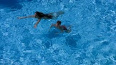 bronzeado : Two kids swim in pool together