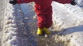 lamacento : Kid in rainboots jumping in the ice puddle
