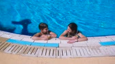 bronzeada : two kids relaxing with cocktail on swimming pool