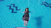 immerse : Young girl in dress falling to swimming pool Stock Footage