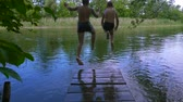 irmãos : Two boys jump together to the river from pier