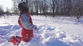 park : funny kid playing with snowballs on winter park