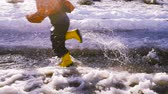 iszapos : Kid running at the spring creek with melting ice