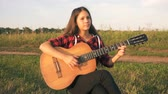 Young girl playing guitar on meadow at the sunset