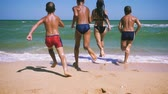 Four kids running to the sea from the beach Vídeos