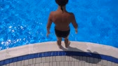 Boy jumping to blue pool, slow motion, aerial view Vídeos