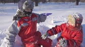 Two kids on winter park with sticky snow glowes