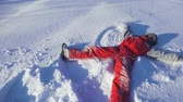 Happy boy on winter park making snow angel