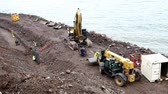 escavação : DULUTH, MN - October 26, 2018: Caterpillar and construction workers install new pilings to repair weather damage along shore of Lake Superior. 2 clips.