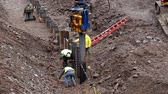 kaynakçı : DULUTH, MN - October 26, 2018: Caterpillar and construction workers install new pilings to repair weather damage along shore of Lake Superior.