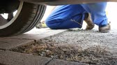substituição : A man in work trousers replaces a car wheel,Wheels of summer tires for winter