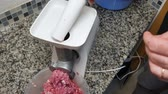 abattage : A man twists pork meat in an electric meat grinder