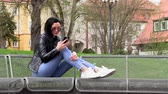 telemóvel : Brunette sits on a street bench and listens to music