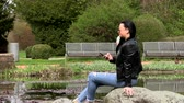 携帯 : Brunette near the lake with a phone 動画素材