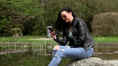 móvel : Brunette near the lake with a phone Stock Footage