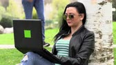 casual sitting : Brunette on the grass with a computer