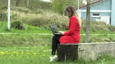 vestido rojo : The girl in the red dress works on the street with a laptop