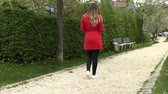 teenagers : Girl in a red dress with a phone on the street in the park Stock Footage
