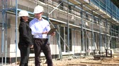 bauunternehmen : Two architects in white helmets discuss a plan at a construction site
