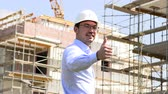 architektura a stavby : Architect at the construction site shows thumbs up