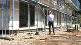 inspetor : Architect inspects construction outside talking on the phone Stock Footage