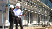 équipe de travail : Two architects in white helmets discuss a plan at a construction site