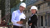 équipe de travail : Two architects a man and a woman in construction in white helmets
