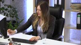 sekretarka : brunette manager works in the office with documents