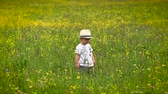игривый : A little boy in a white hat plays a field flower field