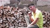 Portrait of a young man sitting near the wood Filmati Stock