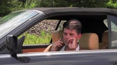sigorta : A young man sits in a broken car and makes phone calls