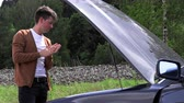 A young man opens the hood of a broken car. Wideo