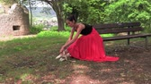 Ballerina tying pointe shoes sitting outside