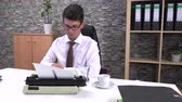 autor : accountant writes on a typewriter at a table in the workplace
