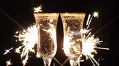 Glasses of champagne and sparklers on bright background with