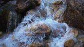 SLOW MOTION: flowing water over stones in mountines river,camera moving down